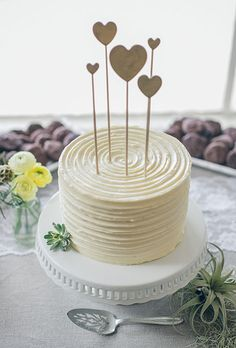 Brides: One-Tier White Cake with Heart Toppers. A simple one-tier white wedding cake with heart toppers created by Cake Monkey Bakery.