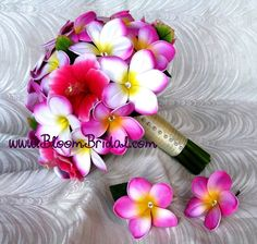 ♥ Joanne L's bridal bouquet made of real touch Plumerias in hot magenta & cherry blossom, and silk rose pink Hibiscus. Accented with clear crystals, dressed in ivory satin and finished with a pearl seam. Matching boutonniere and hair flower in hot magenta Plumerias