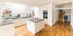 A white matt handleless German kitchen in Alexandra Park, London. The worktop is Silestone and the appliances are Siemens. One of our recent projects. Kitchen Units, David's Kitchen, Alexandra Park, Handleless Kitchen, Integrated Fridge, German Kitchen, Bottle Rack, Hanging Rail, Projects