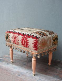 This gorgeous colorful bohemian upholstered wooden Kilim Ottoman would look great anywhere in your hallway, living room, office or bedroom. It is entirely made of wood and it is made in the 1950s. The top and sides are covered with a vintage Kilim, hand woven in Turkey. The wood has been sanded and painted in a soft salmon color to match the warm colors of the Kilim. As a fun finishing touch we used a lovely pompom trim.  It is stable and can be used as a stool, in front of your make up…