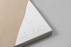 Logotype and print with blind emboss detail by Fable for EAT, the second installation of a two-year long series of exhibitions on Singapore's food culture