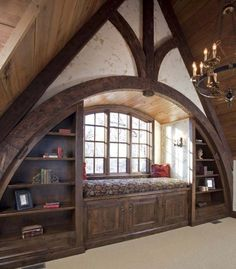 look at the awesomeness of this wall- arched wood beams, recessed cozy window seat, built in bookshelves around the arch - yes please!