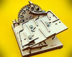 Marbre Machine KIT  Présentation vidéo █ : » https://youtu.be/gpH9aIoLvA0  █ Sur KIT : » Le kit se compose de deux modules: « Electric Mainboad no.1 » & « Bouclier n ° 2 » » Toutes les pièces en bois sont coupées au laser dexcellente qualité ! » Le mécanisme est actionné par un moteur électrique de micro » Le moteur est alimenté par piles AA/R6 1,5 v (non inclus) » Dimensions de la trousse Assemblée : 12 x 15 x 15 cm » Conçu par Marcin Saj  █ composants du KIT : » Les éléments bois » 7 x…