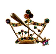 "This brooch pin is made of gold metal. Decorated with purple, green & gold rhinestones. Size 1.5"" length X 1.25"" width"