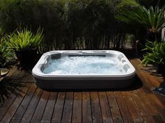 One of our spa models set in a dark wood stained deck. We think the contrast is great!