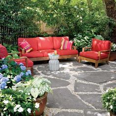 The broken-flagstone-and-pea-gravel patio serves as an extra room. Sofa, chairs, and pillows: Restoration Hardware. Ceramic Lotus stool: Amazon
