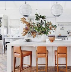 Likey this kitchen, the bar stools, lighting and magnolia arrangement!