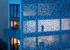 A chequerboard of glass blocks allows light to flood in and out of these creative studios in São Paulo.