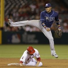 Tampa Bay Rays shortstop Yunel Escobar leaps over Los Angeles Angels' Grant Green after J.B. Shuck grounded into a double play during the fifth inning of a baseball game in Anaheim, Calif., Wednesday, Sept. 4, 2013. (AP Photo/Chris Carlson)
