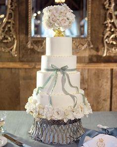 Red velvet wedding cake topped with an urn holding roses, hydrangeas, and gardenias