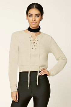 - A heathered knit pullover top featuring a lace-up front with grommets, a round neckline, long sleeves, and ribbed trim.