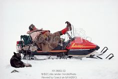 Image of saami reindeer herder, johan logje, rests with his feet up on his snowmobile handlebars. kautokeino. north norway. by ArcticPhoto