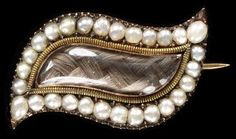 Brooch  Place of origin: England, Great Britain (made)  Date: 1775-1800 (made)  Artist/Maker: unknown (production)  Materials and Techniques: Gold set with pearls and enclosing plaited hair under rock crystal