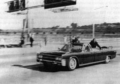 The Presidential limousine bearing Mrs. Kennedy and the slain President speeds towards Parkland Hospital on Friday, 11/22/63.   Clint Hill is positioned above them.