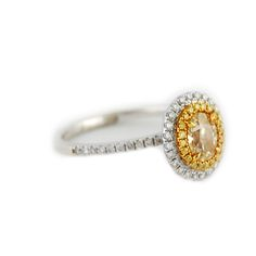 Fancy Yellow Oval Double Halo Diamond Ring Center diamond is .76 carat fancy light yellow VS2 clarity oval cut diamond, certified by EGL US.  The center is accented by a halo of fancy yellow round brilliant diamonds and another halo of white diamonds, with diamond accents in the band as well.  18 karat white and yellow gold.   1.15 ctw