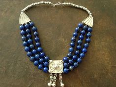 This necklace is a vivid picture of Ethiopian silver Muria(wedding necklace) and good quality lapis lazulli. The lapis is from Afghanistan, 1980.  The center and side pieces newly made in good silver 800/1000 copied from an old Muria necklace by my jeweller in Addis Ababa. A highly skilled jeweller. The back beads are old Wollo beads, of a lower silver conten and the silver beads in between the lapis beads antique and good silver content. The necklace has been durably strung by me. The…