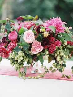 jewel tone wedding centerpiece in shades of deep pinks and purples with ranunculus, dahlias and hops