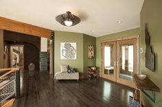 Shoe tree and bench plus Olive green walls and rustic wood elements combine for a charming prelude to the earthy color scheme found throughout the home.