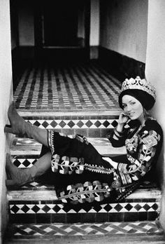Talitha Getty seated on steps wearing Moroccan copper crown, Berber wedding dress, and canvas boots from London. Photographer: Maurice Hogenboom. Location:Marrakech, Morocco. ca. April 1971. A Conde Nast Archive