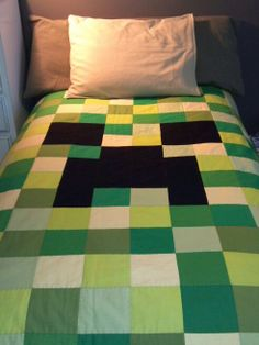 "My first quilt, ever! For this Minecraft Creeper quilt I cut blocks 5"" by 5"", using six different shades of green. (The seventh I forgot about, so ended up using that to make the binding.) There is an eighth shade that I used for the backing. I did 16 squares across and 20 down. I wanted the finished quilt to be big enough to cover an IKEA single/twin duvet underneath it."