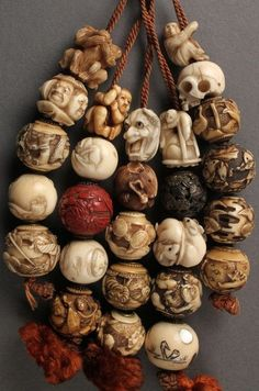 Collection of 26 Asian Ojime beads, strung on a tassel, most ivory, bone, or celluloid, many signed.   Collected by George and Charles Mitchell during the course of several trips to China and Japan in the late 19th-early 20th century.