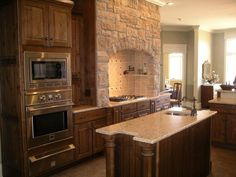 The stacked stone hearth is a beautiful focal point of the kitchen, and it conceals a professional grade Vent-A-Hood.