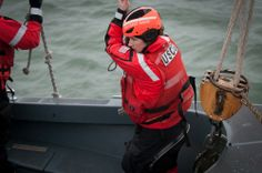 Petty Officer 3rd Class Shelbie Smart holds onto a monkey line while being lowered to the sea in one of Eagle's small boats. U.S. Coast Guard photo by Petty Officer 2nd Class LaNola Stone.