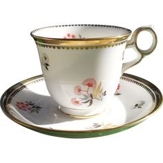 Royal Chelsea footed teacup and saucer features asian style flowers on white ground. Trimmed in 24 kt gold. Pattern No. 4352A Ring handle. No