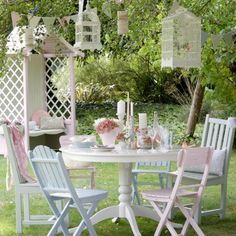 I just love the ice cream colours of these chairs & the birdcages hanging in the trees.