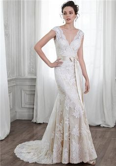 Dreamy lace and tulle adorn this A-Line wedding dress with dramatic V-neckline and back, accented with scallops and adorned with optional ribbon belt at the waist. Finished with covered button over zipper closure.