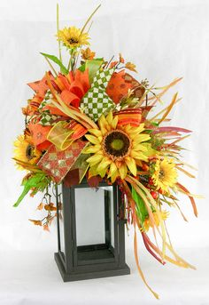 A black metal and glass lantern with a large sunflower swag filled with grasses, honeysuckle vines, and burlap leaves in rust, green and brown. Topped with a six patterned Terri Bow in coordinating ri Fall Lanterns, Christmas Lanterns, Lanterns Decor, Lantern Crafts, Halloween Lanterns, Fall Swags, Fall Wreaths, Adornos Halloween, Fall Flower Arrangements