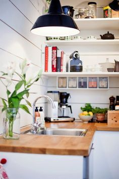 Butcher block counter tops, wood panel wall, industrial light, goose neck faucet with old fashioned knobs, ... bigger quantity dry good storage under the open shelving - genius use of the wall space