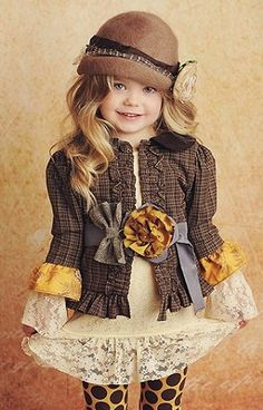 and now for fall fashion ..our model is wearing an ivory lace shirt with brown plaid tailored jacket ...also sporting gray ribbons a brown hat and designer polka dot tights ...with matching golden accents to tie it ALLLL 2 gether .