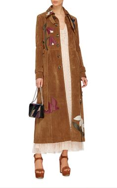 Rendered in suede with leather flower appliques throughout, this **Red Valentino** trench coat features a classic long sleeve design with a standard collar, a tonal self-belt at the waist, and an ankle length boxy silhouette.