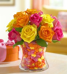 Centerpiece Idea ~ multicolored rose bouquet with a clear vase and add matching candies