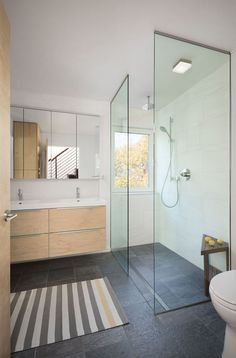 This contemporary bathroom has a glass shower stall with a rain shower head, and a window for looking at the trees while showering.