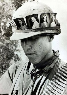 Cu Chi May 1968 - An American soldier keeps a constant reminder of his girlfriend back home, with his helmet band filled with her photograph