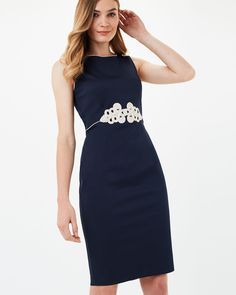 This smart fitted dress is a flattering choice for special occasions. With elegant tapework at the waist and contrast piping at the round neck, this dress is finished with a back zip fastening and full lining.