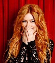 cheveux roux longs bouclés, ondulations romantiques et robe en dentelle noire, rideau rouge et des yeux marron clair