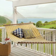 A buttery yellow hammock is the perfect perch on this St. Kitts cottage porch. | Coastalliving.com