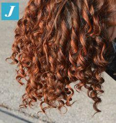 Degradé Joelle con nuances bronzo, rosso e rame esprime al massimo la femminilità sui capelli ricci.