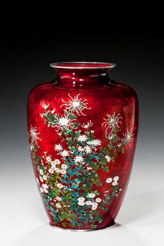 A lovely Japanese Akasuke or 'Pigeon Blood' red cloisonné vase with silver rims to top and bottom, decorated with fine floral cloisonné work with daises and chrysanthemums.