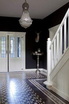 Vloer is druk, maar ruimte is toch stijlvol door hem leeg te laten.  #hal #zwart #wit #interieur #fengshui