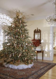 A Christmas tree in the entrance hall is decorated with a collection of Christopher Radko ornaments. - Traditional Home ® / Photo: Gordon Beall