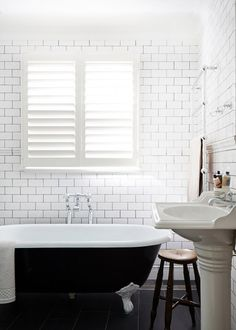 Clawfoot tub painted black with lots of white subway tile.