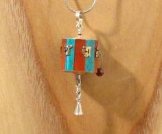 Handgemaakte middelgrote hanger van zilver (925) in de vorm van een gebedsmolen en ingelegd met turquoise steen en rood koraal, afkomstig uit Nepal. De Tibetaanse koperen tekens zijn een mantra en met de hand uitgesneden.