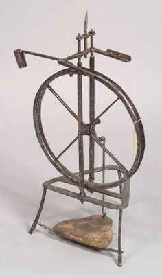 French Iron Spinning Wheel, 18th/19th century, triangular base with wooden foot pedal, the top of wheel with fleur de -lys clamp, ht. 33 3/4 in.
