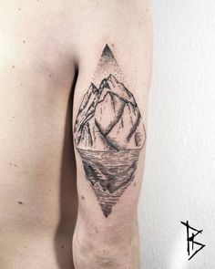 Engraving style landscape rhombus tattoo on the back of the right arm.