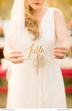 Gold lettering on a glass or perspex sheet for table numbers! We love this idea!!