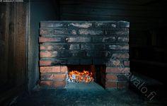 Savusaunan kiuas lämpenee - suomalainen savusauna sauna hämärä nokinen musta mustunut tummunut noki vanha savusaunan kiuas muurattu tiilistä tiilinen tiili tiilet tiilikiuas lämmittää kiuasta saunaa polttaa puita hiillos kuuma tulinen oranssi punainen punahehkuinen hehku hehkuva hehkuvat kuumuus kekäle hiili hiilet hehkua polttavan tulikuuma tuli lämpö saunan lämmitys lämmittäminen energia lämpöenergia puu puuaines puuta puunpoltto puun polttaminen palaa tuottaa lämpöä saunanlämmitys
